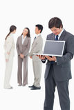 Salesman showing notebook screen with team behind him Royalty Free Stock Images