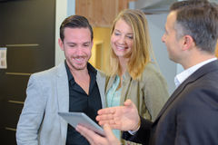 Salesman showing screen tablet to couple royalty free stock image