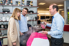 Salesman Showing Steam Iron To Couple In Hypermarket Stock Photos