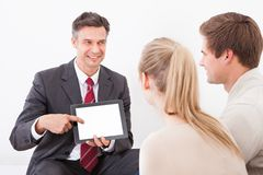Salesman showing tablet pc to couple Stock Photos