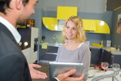 Salesman showing tablet screen to customer. Salesman stock images