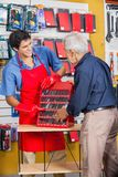 Salesman Showing Tools To Senior Man In Store. Smiling salesman showing tools to senior men in hardware store Stock Photography