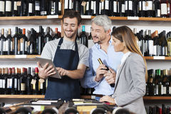 Salesman Showing Wine Information To Couple On Digital Tablet Royalty Free Stock Photography