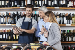 Salesman Showing Wine Information To Customers On Digital Tablet. Smiling young salesman showing wine information to customers on digital tablet in shop royalty free stock photo