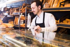 Salesman shows bakery pastries Stock Images
