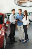 Salesman shows information for clients. Salesman shows information about the car for his new clients stock photo