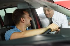 Salesman shows options for client. Client sitting in the car. Car is red. They are in car dealership stock photo