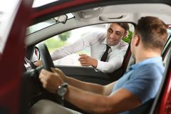 Salesman shows options for client. Client sitting in the car. Car is red. They are in car dealership royalty free stock photography