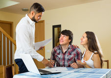 Salesman signs contract with couple Stock Photography