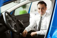 Salesman is sitting in brand new car. He is in white shirt. Car is in blue colour stock photo