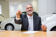 Salesman sitting while offering car keys Stock Photo