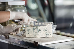 Salesman Slicing Blue Cheese With Knife Stock Image