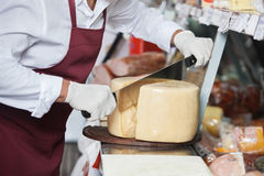 Salesman Slicing Cheese With Double Handled Knife. Midsection of salesman slicing cheese with double handled knife at counter Stock Photo