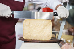 Salesman Slicing Cheese With Double Handled Knife Royalty Free Stock Photos