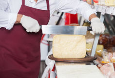 Salesman Slicing Cheese With Double Handled Knife Stock Photo