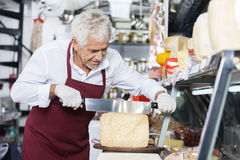 Salesman Slicing Cheese With Double Handled Knife In Shop Stock Photo
