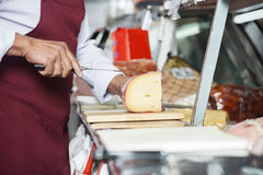 Salesman Slicing Cheese In Shop. Midsection of salesman slicing cheese at counter in shop Royalty Free Stock Image