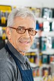 Salesman Smiling In Hardware Store. Closeup portrait of senior salesman smiling in hardware store Stock Photo