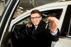 Salesman smiling holds car keys in car. Salesman smiling holds car keys in car in auto salon stock photography