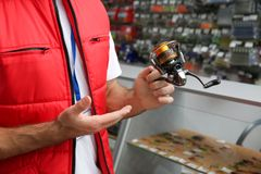 Salesman with spinning reel in sports shop, closeup. Fishing equipment stock images