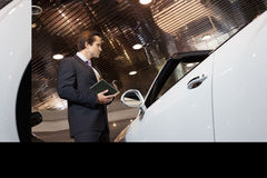Salesman standing in automobile showroom Stock Photo