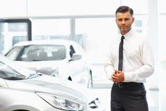 Salesman standing in car retail store. Car Showroom. Stock Photo