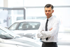 Salesman standing in car retail store. Car Showroom. Royalty Free Stock Image