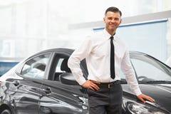 Salesman standing in car retail store. Car Showroom. Salesman standing in car retail store. Car Showroom stock image
