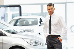 Salesman standing in car retail store. Car Showroom. Stock Photos
