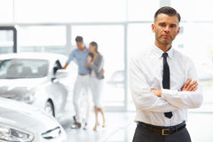 Salesman standing in car retail store. Car Showroom. Royalty Free Stock Images