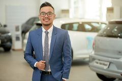 Salesman standing in car showroom. Portrait of Asian salesman in suit standing in car showroom and smiling at camera royalty free stock images