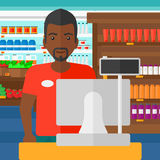 Salesman standing  at checkout. Royalty Free Stock Image