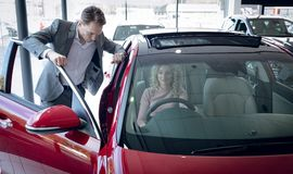 Salesman standing by customer sitting in car. At showroom stock images