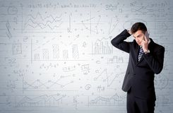 Salesman standing with drawn graph charts. A confident young businessman standing in front of wall with drawn pie charts, graphs, numbers, arrows concept Stock Image