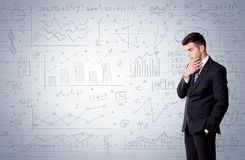 Salesman standing with drawn graph charts. A confident young businessman standing in front of wall with drawn pie charts, graphs, numbers, arrows concept Stock Photography