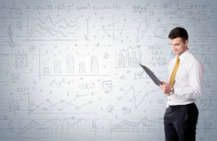Salesman standing with drawn graph charts. A confident young businessman standing in front of wall with drawn pie charts, graphs, numbers, arrows concept Royalty Free Stock Images