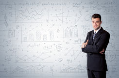 Salesman standing with drawn graph charts. A confident young businessman standing in front of wall with drawn pie charts, graphs, numbers, arrows concept Stock Photo