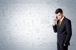 Salesman standing with drawn graph charts. A confident young businessman standing in front of wall with drawn pie charts, graphs, numbers, arrows concept Royalty Free Stock Image