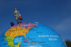 Salesman standing on globe Stock Photo