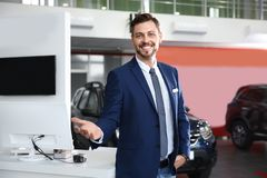 Salesman standing in modern auto dealership. Buying new car royalty free stock images