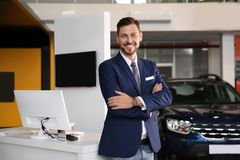 Salesman standing in modern auto dealership. Buying new car stock image