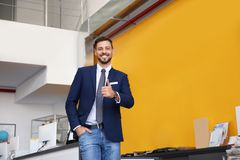 Salesman standing in modern auto dealership. Buying new car royalty free stock photos