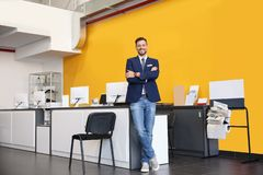 Salesman standing in modern auto dealership. Buying new car stock photography