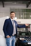 Salesman standing in modern auto dealership. Buying new car stock photos