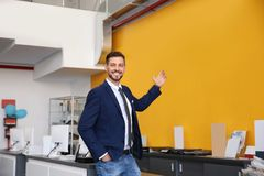 Salesman standing in modern auto dealership. Buying new car royalty free stock image