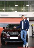 Salesman standing in modern auto dealership. Buying new car stock photo