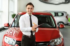Salesman stay near car. He is waiting for clients. Car is red. He holds tablet in hand. He is smiling stock photography