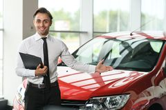 Salesman stay near car. He is waiting for clients. Car is red. He holds tablet in hand. He is smiling. He shows with his hand on brandnew car royalty free stock image
