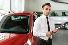 Salesman stay near car. He is waiting for clients. Car is red. He holds tablet in hand stock photography