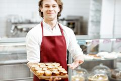 Salesman with sweet cakes at the pastry shop. Portrait of a handsome salesman or confectioner in red apron standing with fresh baked pastel de nata in the pastry stock images
